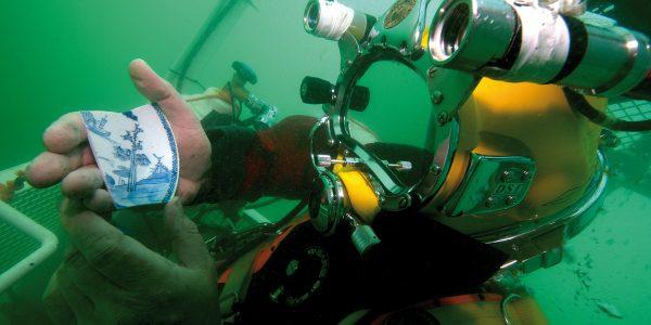 Een duiker laat een stuk porselein uit het wrak van het VOC-schip de Rooswijk zien. Foto Rooswijk1740 project/Rijksdienst voor het Cultureel Erfgoed.